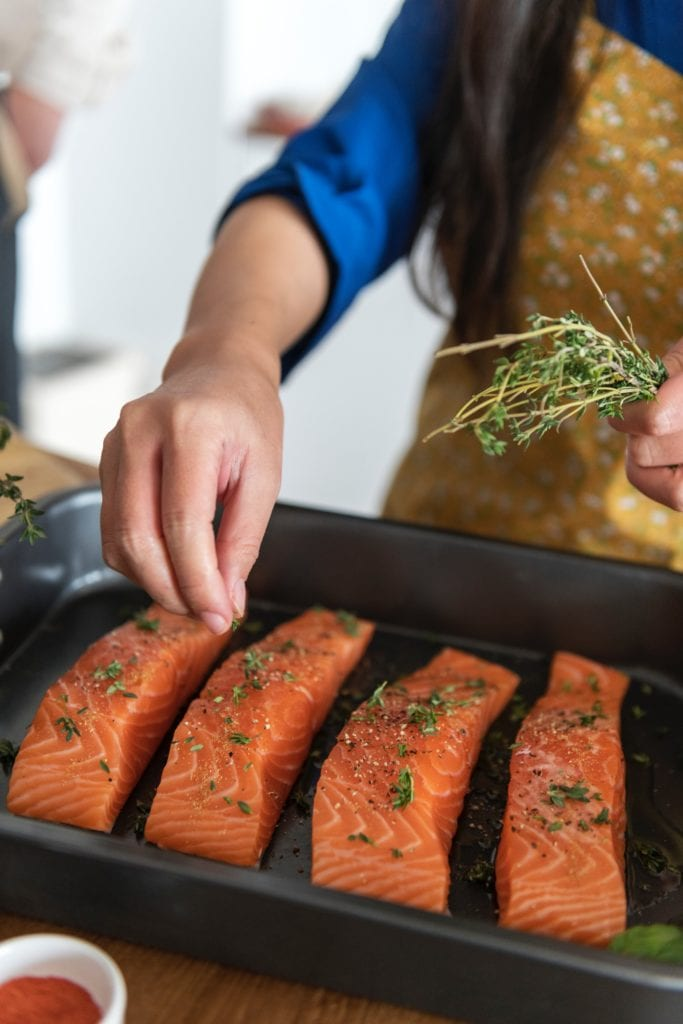 Salmon B12 - Person cooking salmon steaks a great source of vitamin b12.